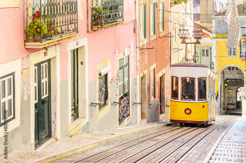 Leinwandbild Motiv Traditional yellow trams on a street in Lisbon, Portugal