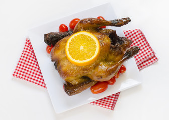 Roasted chicken with sliced orange and cherry tomatos