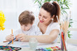 Happy smiling mother and child drawing together