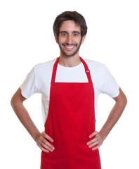 Lachender Kellner mit Bart und roter Schürze