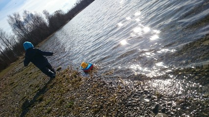 Kind an see zieht spielzeugboot