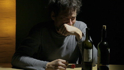 Desperate sad man looking two empty bottle