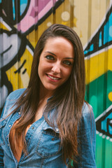 Young Woman Smiling in front of a Graffiti Wall