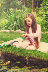 Little girl feeds fishes