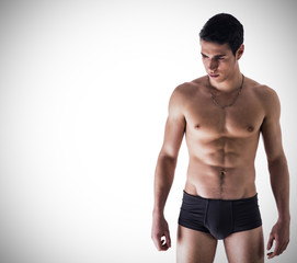 Handsome, fit young man in underwear on white background