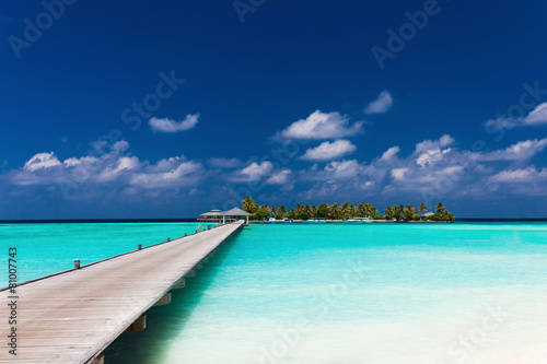 Fototapeta Wooden jetty to a tropical island over lagoon in Maldives