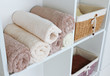 Rolled towels with wicker basket on shelf of rack background - 81008383
