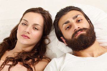 Couple strained relations, lying on bed sad expression