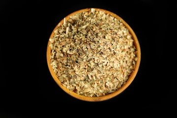 Dried parsley in wooden bowl, isolated on black