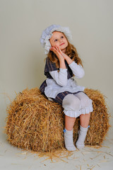 Girl in dress sitting on a rustic vintage straw bale