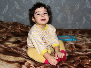 Small child sits on blanket, crossing her legs
