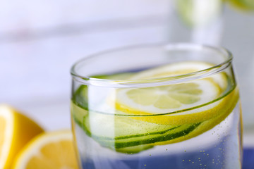 Fresh water with lemon and cucumber in glass, closeup