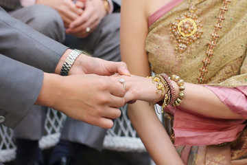 groom put the wedding ring into bride hand