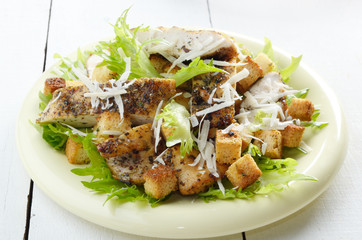 Caesar chicken salad on white table