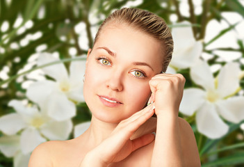 Портрет красивой молодой женщины на фоне цветов