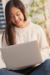 Asian smiling woman is working with notebook at home