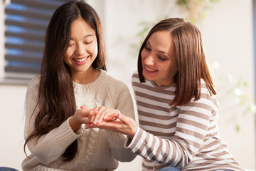 Asian woman is showing her wedding ring to her friend