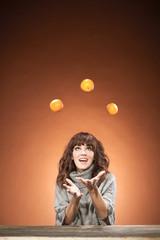 Caucasian brunette woman is juggling oranges