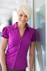 Blonde smiling woman next to a glass wall