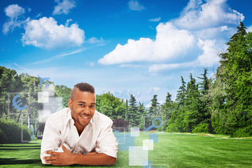 Smiling african man is lying on a green field