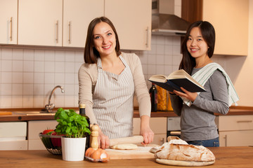 Woman is working on a dough while her friend is reading a cookbo