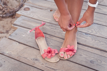A girl putting on coral sandals at the beach sundeck