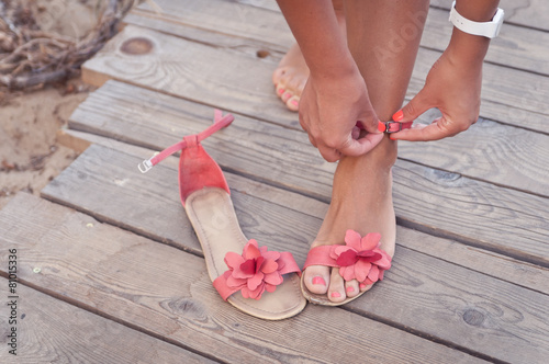 A girl putting on coral sandals at the beach sundeck - 81015336