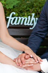 The newlyweds joined hands and sit on the bench.