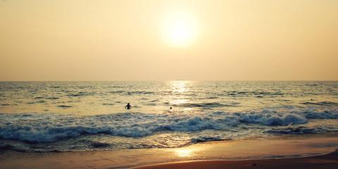 A few tourists on the tropical ocean beach - retro effect. Sunse