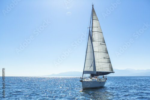 Fotografiet Sailing ship yachts with white sails in the open Sea.