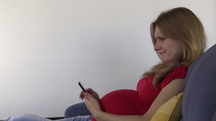 Cute pregnant woman browse photos and internet with smartphone