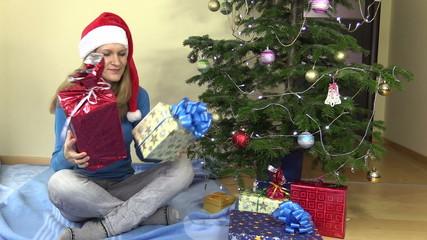 female girl check shake gift present boxes near Christmas tree