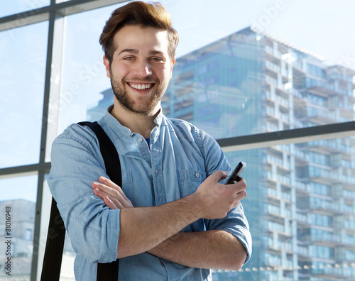 Leinwanddruck Bild Handsome young man smiling with mobile phone