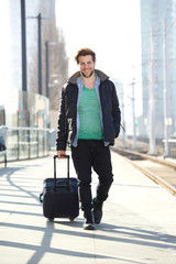 Happy man walking on train station platform with bag
