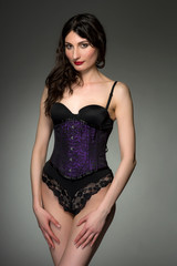 Young woman in purple corset and black lingerie