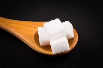 White refined sugar in wooden spoon