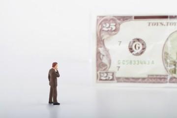 miniatura di uomo d'affari davanti a banconota
