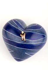 donna sola in miniatura seduta su un cuore blu di pietra