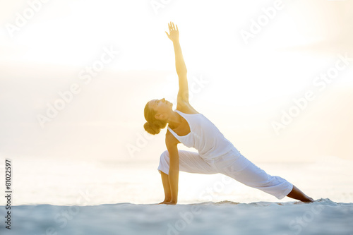 Fotobehang Gymnastiek Caucasian woman practicing yoga at seashore