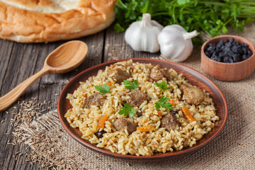 Traditional uzbek meal pilaf. Rice with meat, carrot and onion