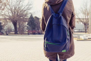 Rear view of hipster girl with backpack, copyspace