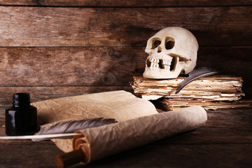 Still life with human skull, retro book and quill