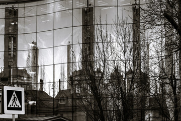 Old city reflecting in mirror wall of new building
