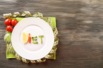 Word DIET made of sliced vegetables in plate with measuring