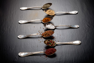 Old metal spoons with different kind of spices on a black backgr