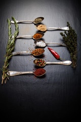 Herbs and spices with old metal spoons on a black background