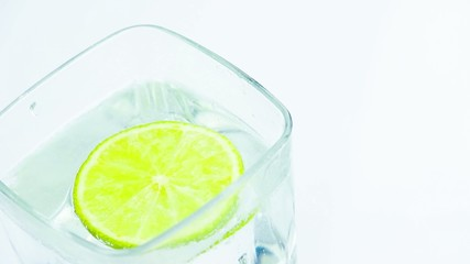 sparkling water in the glass with bubbles and lime