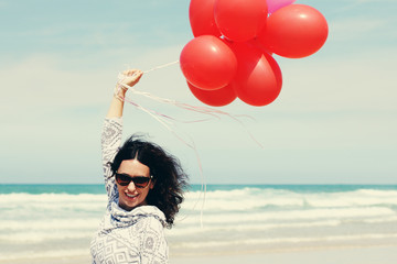 beautiful woman holding red balloons