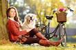 Pretty female sitting down with her labrador retriever dog in a