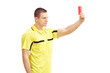 Young football referee in yellow dress showing a red card
